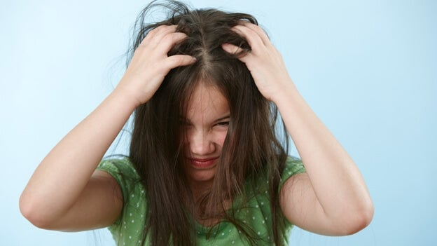 Menina coçando a cabeça; dica para evitar os piolhos
