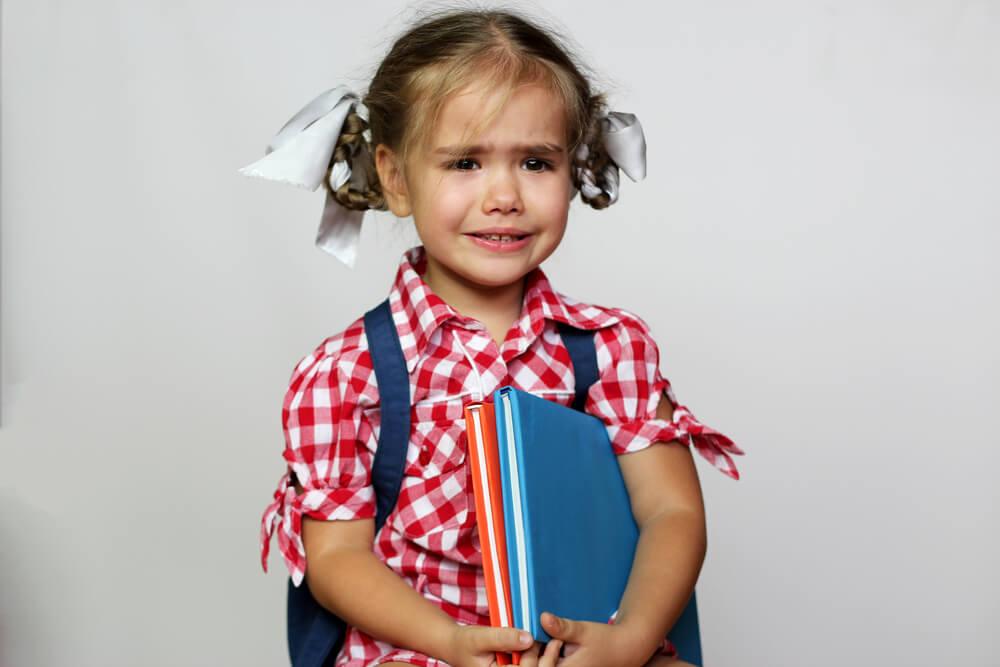 menina chorando e segurando seus livros