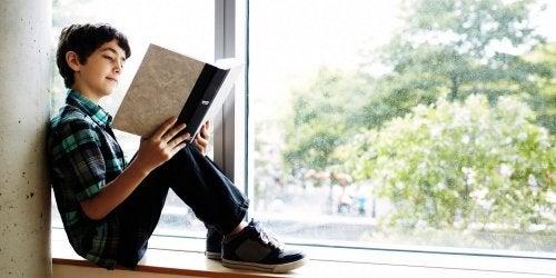 menino lendo um livro na sacada de sua casa