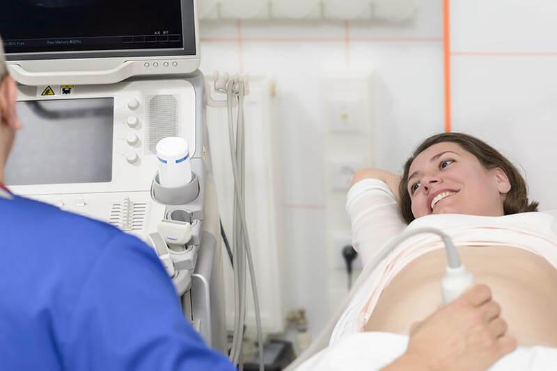 médico fazendo uma ultrassonografia em mulher grávida