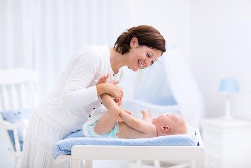 mãe brincando com o bebê no trocador