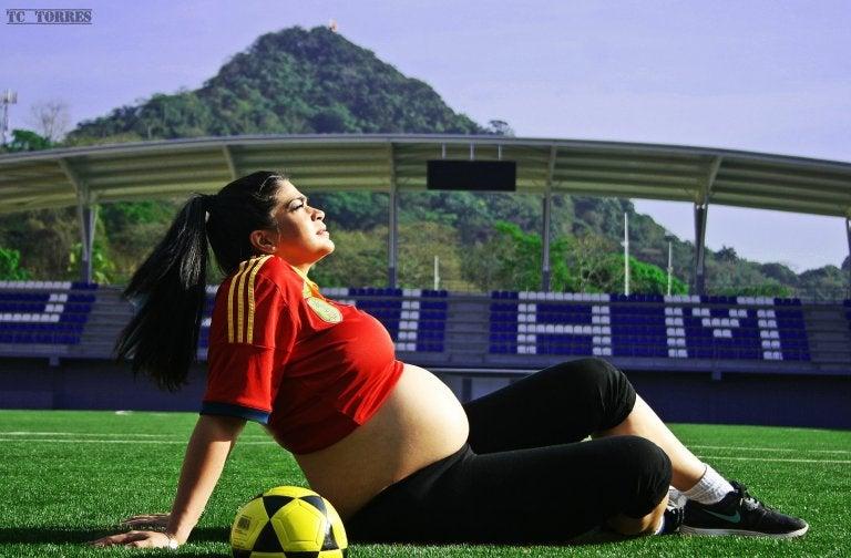 mulher grávida sentada em um campo de futebol
