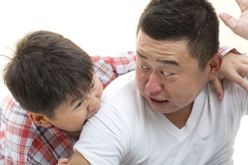 Filho mordendo as costas do pai