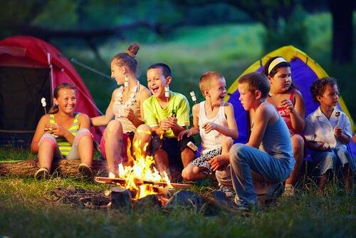 crianças ao redor de uma fogueira assando marshmallow e os ditados populares