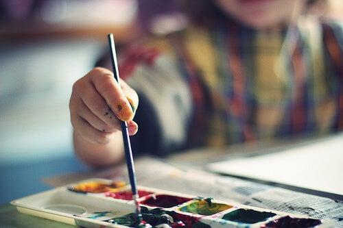 Criança pintando e exercitando a coordenação motora