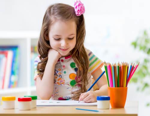 Destro ou canhoto, menina pintando com lápis de cor