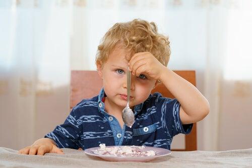 Destro ou canhoto, menino canhoto com a comida