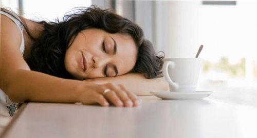 mulher dormindo com uma xícara de café na sua frente, método japonês contra a preguiça