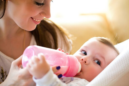 mãe dando leite na mamadeira para o bebe faz parte do aleitamento misto