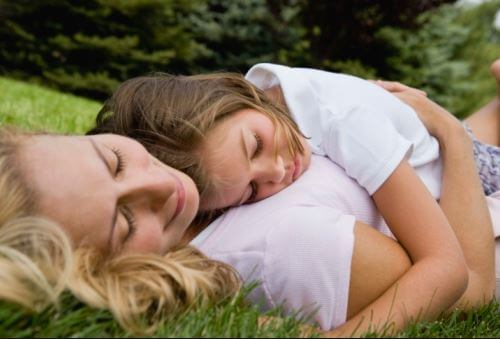 Mãe deitada na grama com filha