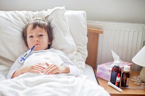 menino doente com termômetro na boca, bronquite
