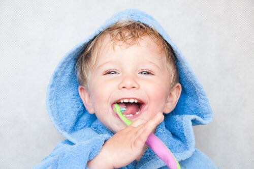 Menino escovando os dentes para evitar as cáries de mamadeira