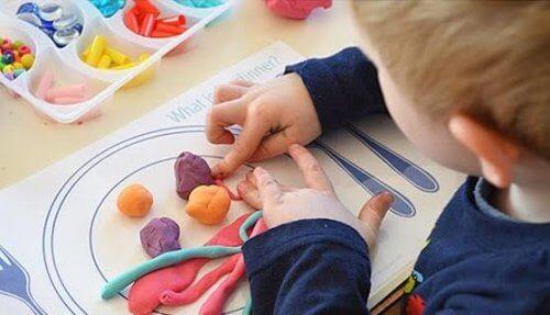 criança brincando com massinha, brincadeiras simples