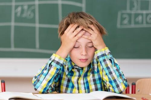 menino com dor de cabeça estudando