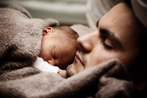 Pai dormindo com o filho para fazer o bebê dormir