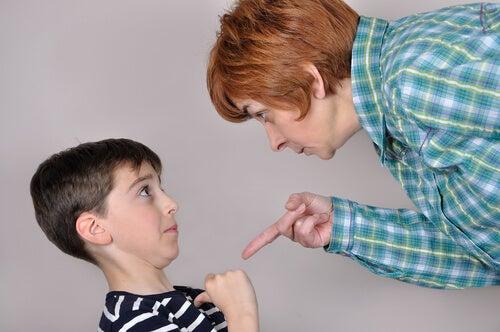 Mãe intimidante apontando para o filho