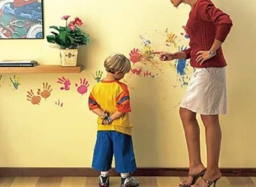 Mãe brigando com criança por sujar a parede