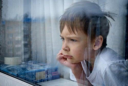 criança olhando atraves da janela em dia de chuva