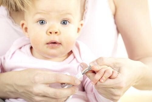 mãe cortando unhas do bebê