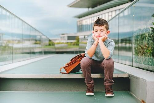 menino triste com a mochila escolar