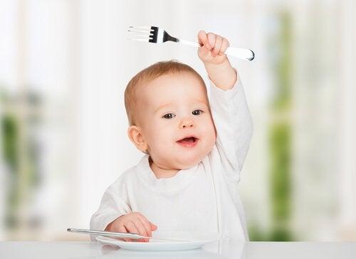 bebê feliz segurando garfo