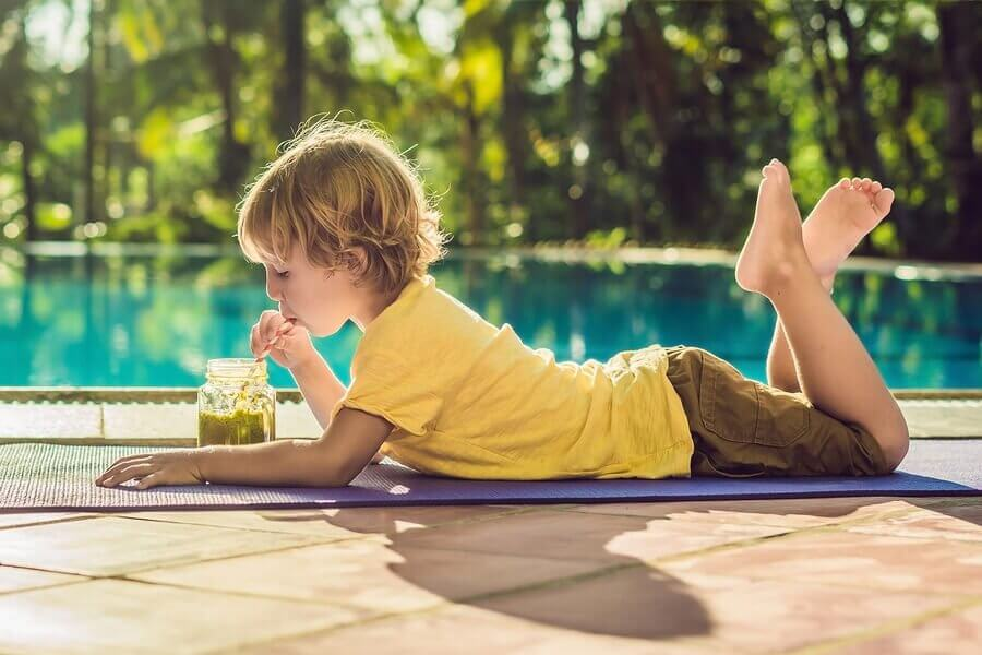 criança tomando um shake de frutas na piscina no verão