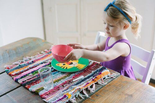 Menina arrumando os pratos