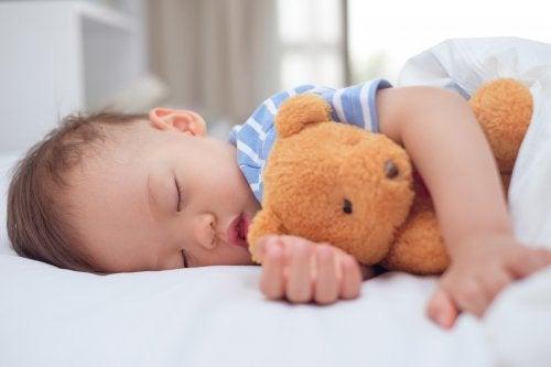 criança dormindo com ursinho