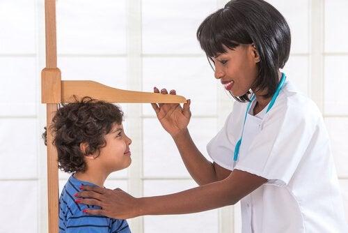 médico medindo a estatura do menino