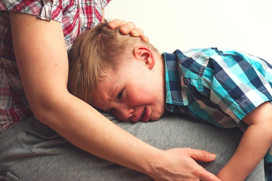 menino chorando no colo da mãe