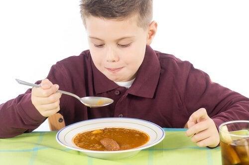 menino tomando sopa de lentilha