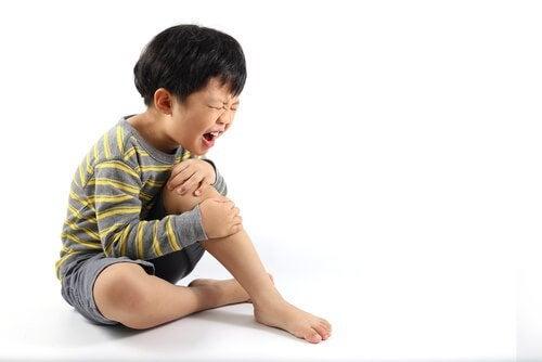 menino com dores no joelho