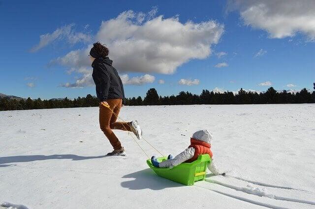 mãe e filha brincando com trenó na neve