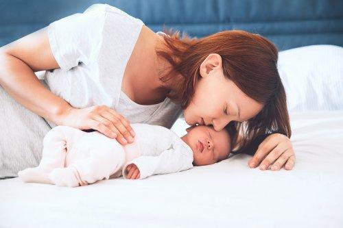 mãe beijando filha recém-nascida