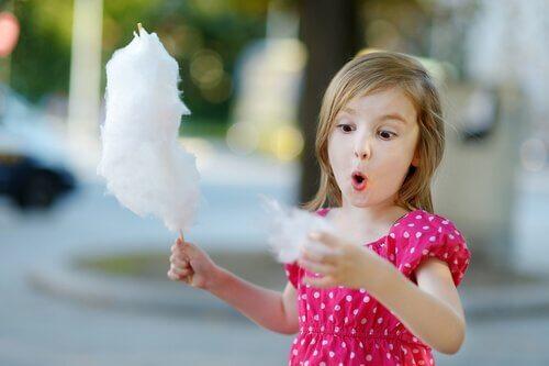 menina comendo algodão doce