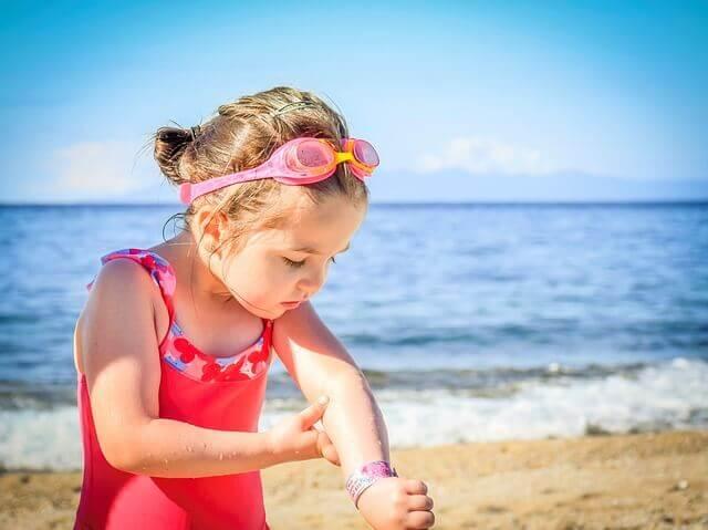 menina passando filtro solar