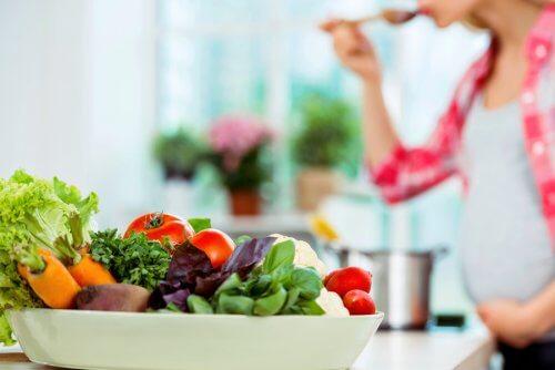 grávida preparando salada verde