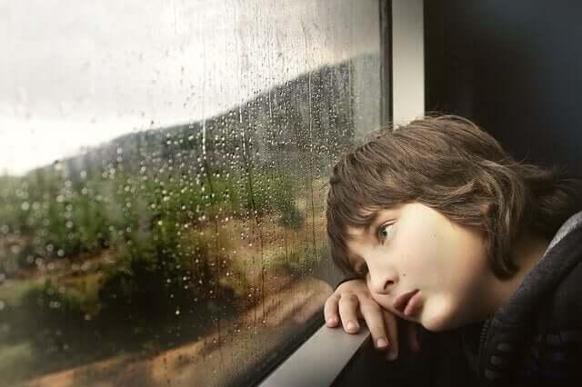 Criança cansada olhando a chuva na janela