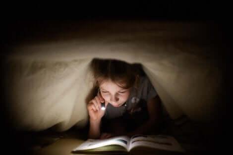 Menina lendo livro da coleção Abra e Descubra