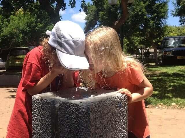 Crianças bebendo água numa tarde de verão
