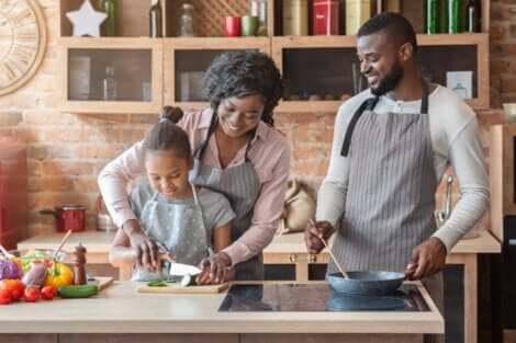 Educar as crianças pelo exemplo: pais e filha cozinhando juntos