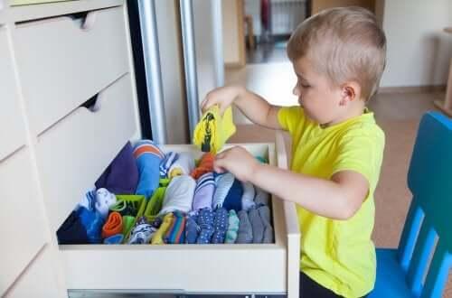 A promoção da autonomia na infância: menino guardando suas roupas