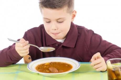 Menino comendo canja porque está com dor de barriga