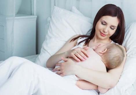 Método da lactação e amenorreia: mãe olhando bebê mamar