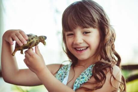Menina segurando uma tartaruga e sorrindo feliz