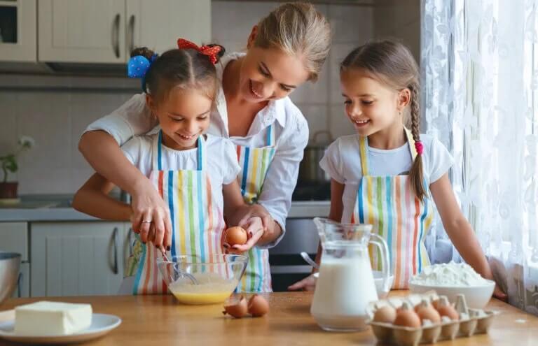 Mãe cozinhando com filhas durante o isolamento por coronavírus