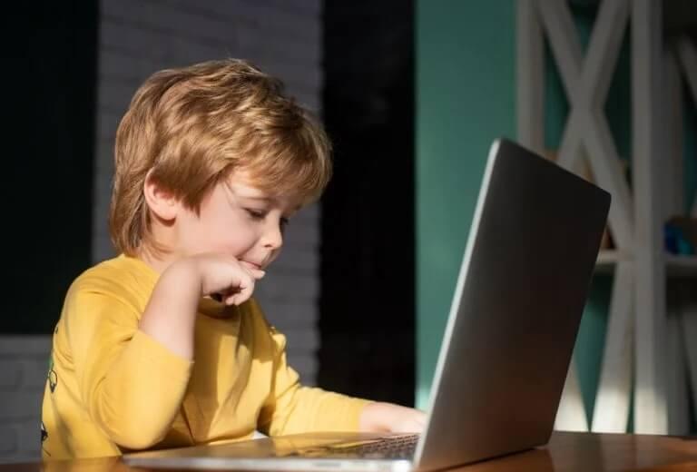 Menino se distraindo no notebool: como a tecnologia nos ajuda durante a quarentena