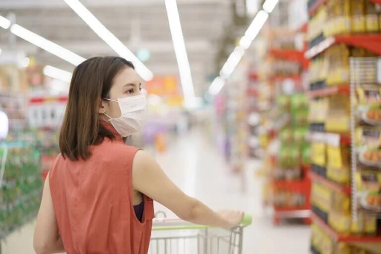 Mulher de máscara fazendo compras