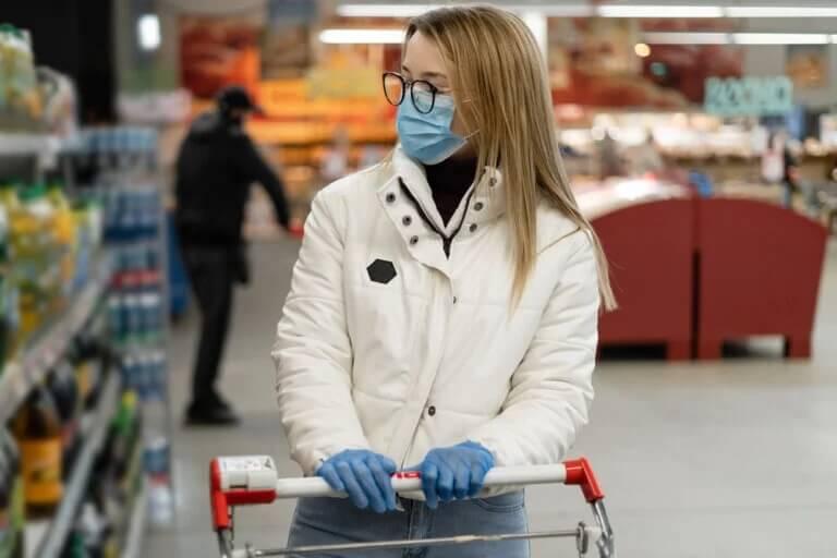 Mulher de máscara e luvas; fazer compras durante o confinamento