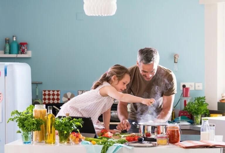 Pai e filha cozinhando em casa
